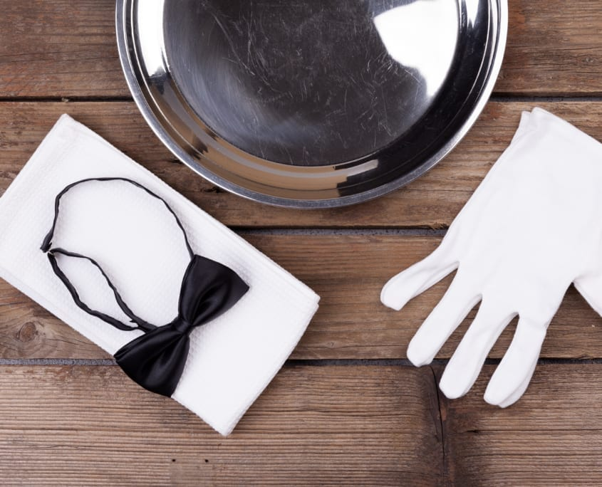 Jamaica villas Top view of a waiter tray, bow tie, gloves and a napkin on wooden background